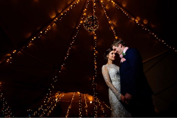 Wedding photo of bride & groom inside of Tipi with lighting