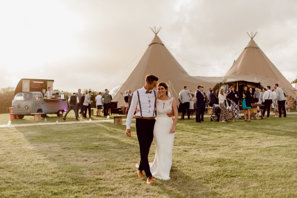 bride & groom walking away from tipi